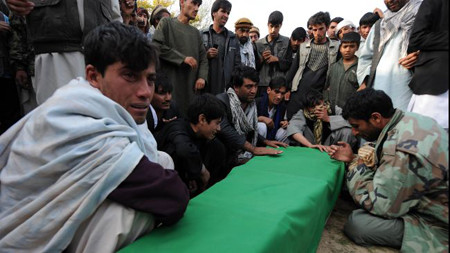 Afghan relatives cry over the coffins of victims who died in a fuel tanker blast near Bagram air base some 50kms north of Kabul, October 26, 2011