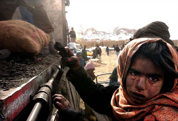 Covered in coal dust, an Afghan girl grabs spilled charcoal at an aid relief distribution in Kabul