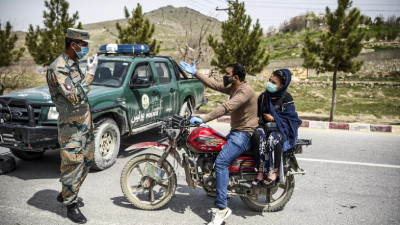 A security personnel stops motorists at a checkpoint during a government-imposed lockdown in Kabul