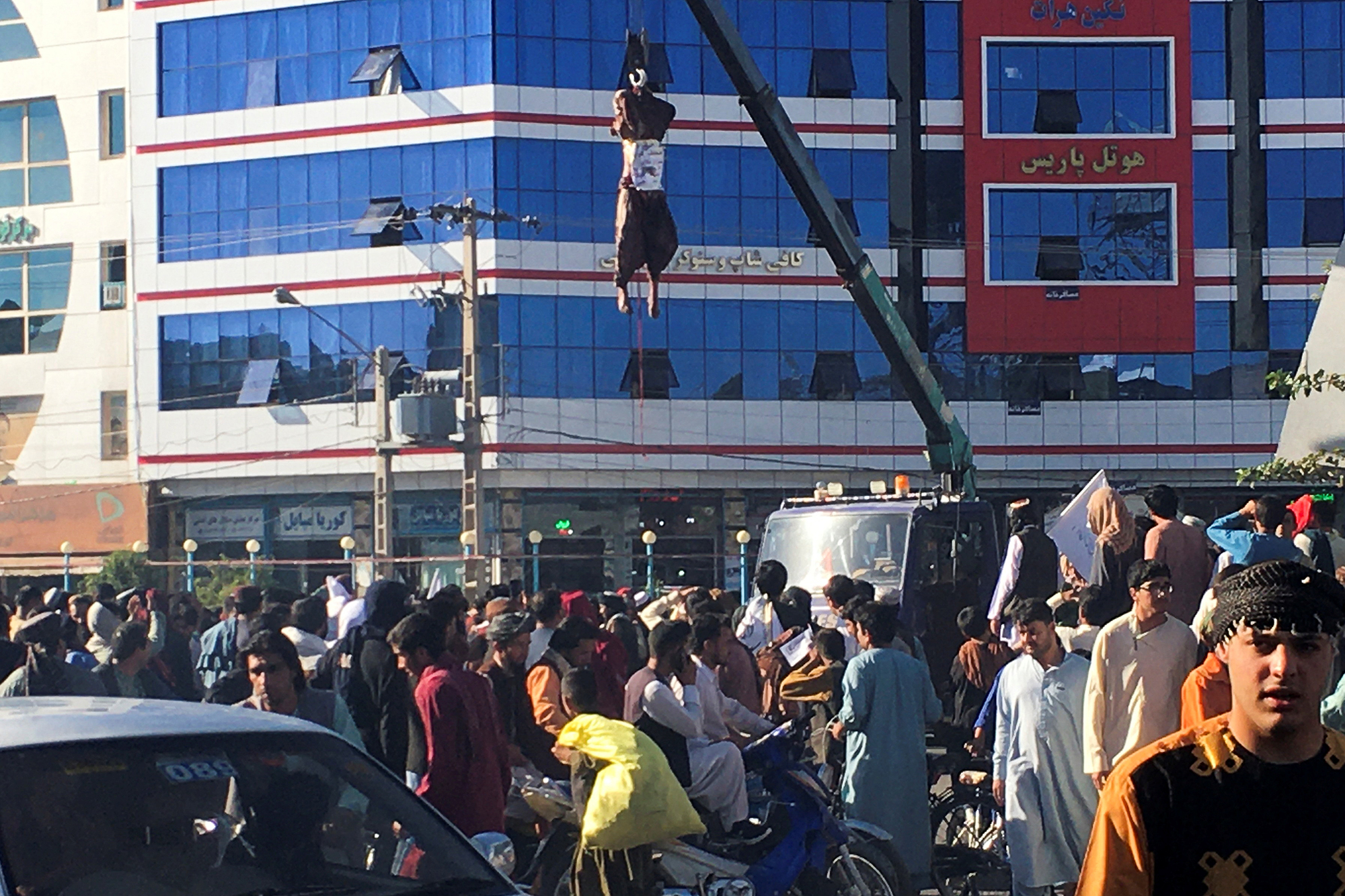 Crowds gather to witness a dead man hanged by the Taliban