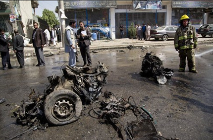 An Afghan fireman stands next to the debris of a car at the scene where a suicide car bomber attacked a NATO convoy in Kabul, Afghanistan, Thursday, May 16, 2013
