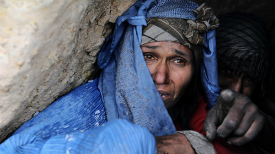 An Afghan woman addicted to drugs looks out from her hut on the outskirts of Herat, in western Afghanistan