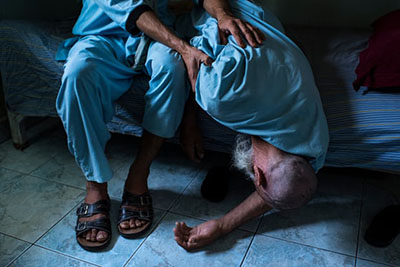 An elderly man falls from his bunk at the drug treatment centre in the provincial capital, Lashkar Gah
