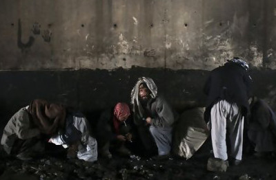 Afghan drug addicts cover their heads with scarves as they use drugs under a bridge inhabited by drug addicts in Kabul
