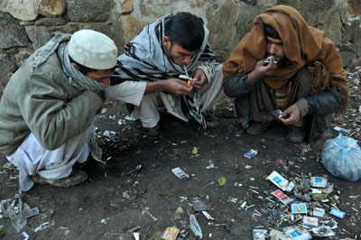 Afghan drug addicts smoke heroin on a street in Jalalabad