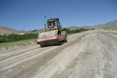 In this July 2009 photograph, an Afghan construction crew works on a planned 17.5-mile, U.S.-funded road in Ghazni province