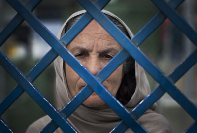 Picture taken March 28, 2013 shows Afghan female prisoner Fauzia steering out of the prison bars at Badam Bagh, Afghanistan's central women's prison, in Kabul, Afghanistan