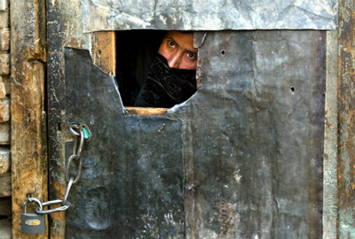 A female inmate peers out the front door as she waits to be released from the women's prison in Kabul