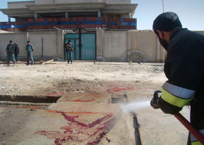An Afghan firefighter cleans bloodstains from the scene of a bomb blast in Lashkar Gah, Helmand province