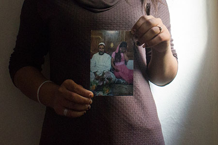 Firoza, 14, holds a photo taken at her wedding three years ago when she was given as a child bride to an old man