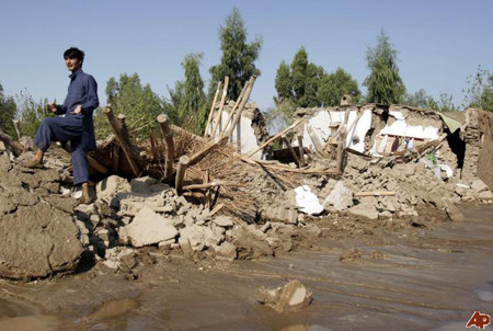 An Afghan man stands near his house which was destroyed by an early morning flash flood on the outskirts of Jalalabad, Afghanistan