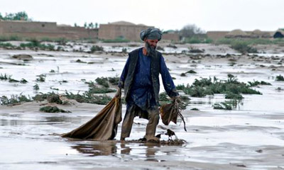 A man carries his belongings after floods devastated Jawzjan, Afghanistan
