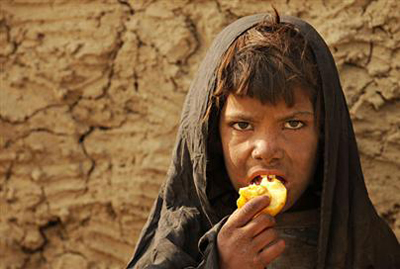 Girl eating fruit outside camp of displaced
