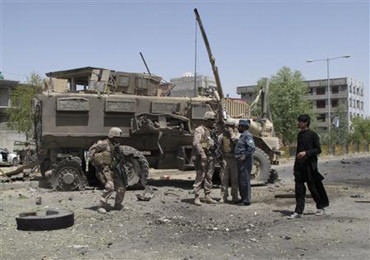 NATO soldiers with the International Security Assistance Force (ISAF) stand at the site of an attack in Helmand province
