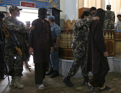 In a Kabul court room, officials escort two of the seven men accused of raping and robbing four women in Paghman district, Afghanistan