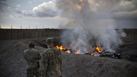U.S. Army soldiers watch garbage burn in a burn pit at Forward Operating Base Azzizulah in Maiwand District