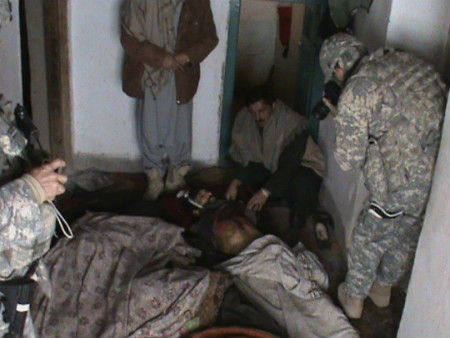 A U.S. soldier takes photographs inside a room where members of an Afghan family were killed near Gardez in Afghanistan's Paktia province by US forces