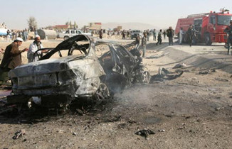 Afghan people gather at the vehicle blown by a suicide bomb in Ghazni province