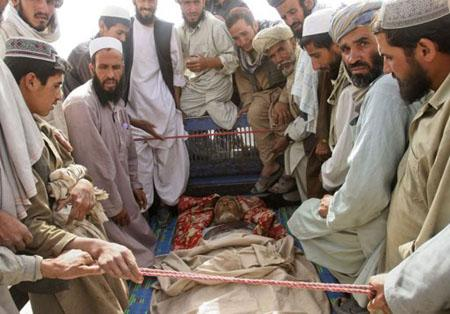 Afghans gather around the body of a man who they claim was a civilian but killed by the NATO forces, during a protest in Ghazni province August 8, 2011