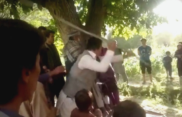 Still from video showing a man publicly beating a girl tied to a tree who was accused of stealing