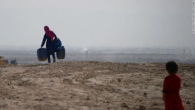 A girl carries empty containers to collect water in Mazar-i-Sharif, Afghanistan