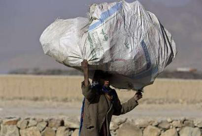 Girl carries rubbish on her head in Kabul