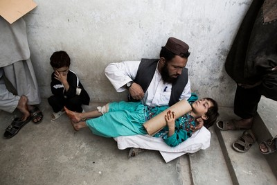 >An Afghan man holds his 8 year old daughter waiting in line for an appointment, Afghanistan