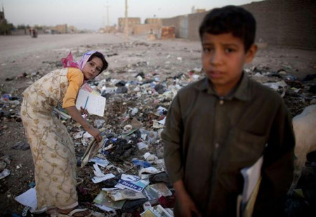 Afghan children rumage through trash to be used as fuel for fire in Herat, Afghanistan