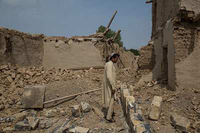 Badshah Dullah stands in what is left of his house that was hit by a U.S. airstrike 15 years ago