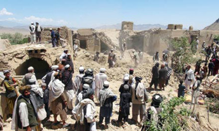 Afghan villagers gather at a house destroyed in a Nato raid in Logar province