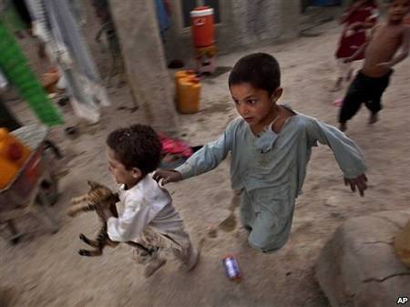 Internally displaced children play at a refugee camp in Kabul in early August