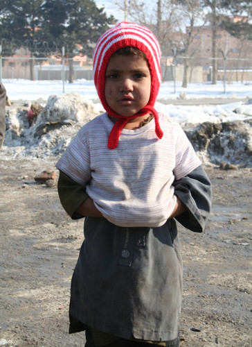 A child stands scantily dressed in blistering cold in the Helmandi IDPs camp in Kabul