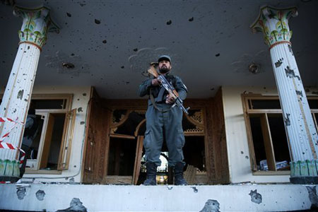 An Afghan policeman stands guard in front of an Independent Elections Commission (IEC) building after a gun battle between security forces and insurgents in Kabul, Afghanistan