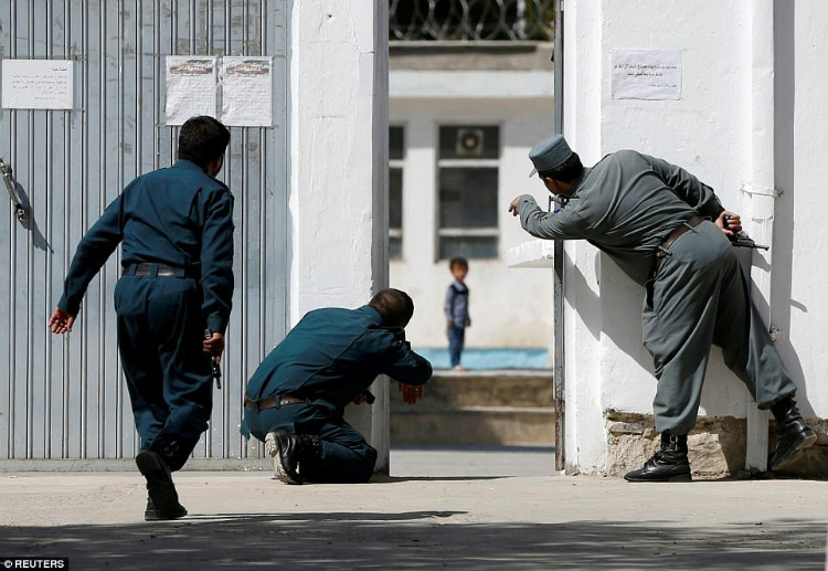 Afghan policemen try to rescue four-year-old Ali Ahmad at the site of a suicide attack followed by a clash between Afghan forces and terrorists after an attack on a Shiite Muslim mosque in Kabul, Afghanistan