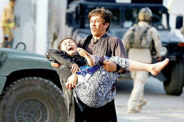 An Afghan man carries an injured woman who is screaming in pain in a blood-stained dress from the site of a suicide attack where 28 men were killed