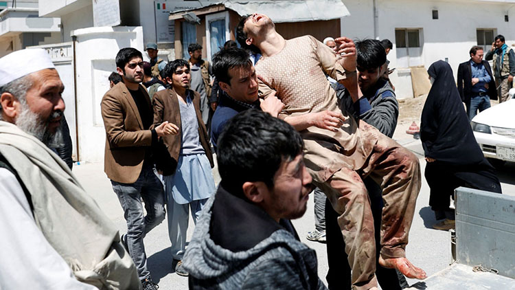 Relatives of victims carry an injured man outside a hospital in Kabul