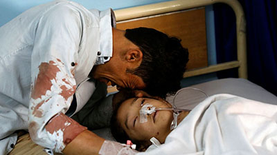 A man cries beside a wounded girl at a hospital after the attack in Kabul