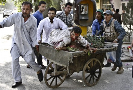 Afghans rush a wounded man to receive treatment, after a suicide car bomber struck outside the Afghan Supreme Court in Kabul