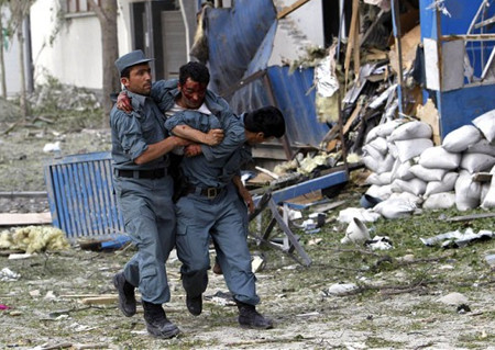 A wounded Afghan policeman is helped away from the site of an explosion in Kabul on May 24, 2013