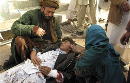 A mother touches her wounded son after a suicide attack in Emam Saheb district of Kunduz province Feb. 21, 2011