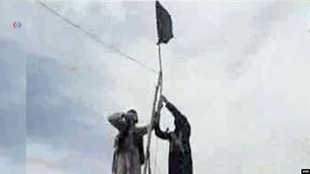 Members of the IS-Khorasan group mount a flag in a tribal region of Afghanistan