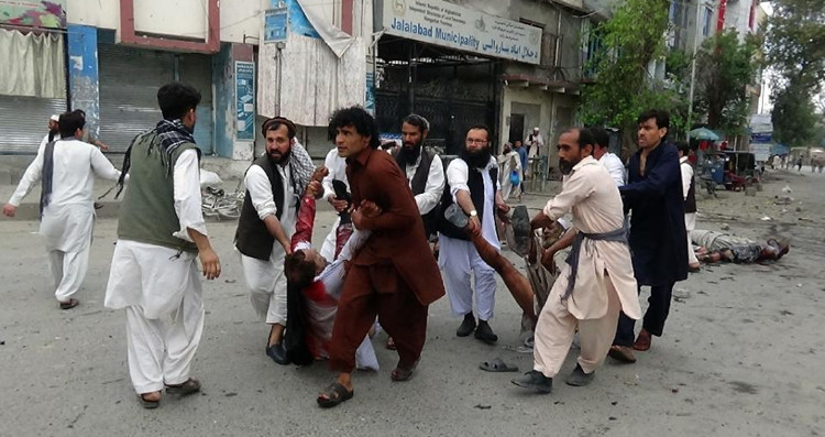 People carry the injured from the site of a blast in Jalalabad, eastern Afghanistan