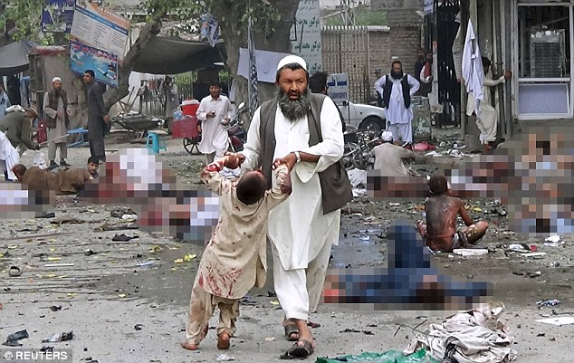 A man leads an injured boy by the hands after a blast in Jalalabad, eastern Afghanistan