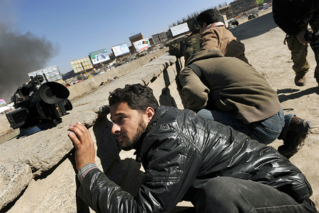 Afghan journalists seek cover in Kabul on Jan. 18, 2010 during a series of co-ordinated attacks by Taliban militants in the Afghan capital