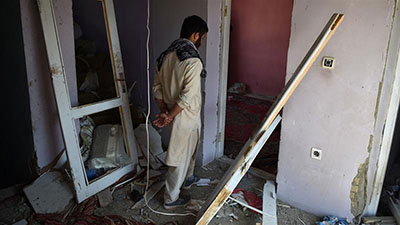 A Kabul resident walks through a damaged house following a NATO air raid