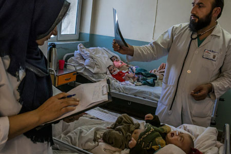 A doctor reviewed the X-ray of a sick child in a hospital managed by the French aid organization Doctors Without Borders in Kabul, Afghanistan