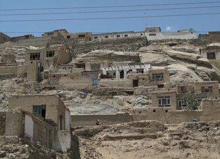 Poorly constructed houses cling precariously to hillsides in Kabul