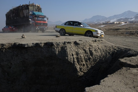 Vehicles navigate a stretch of Highway One, damaged by a roadside bomb, in Sayed Abad, Afghanistan