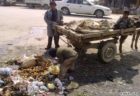 A poor Afghan child collects foot from garbage in Kabul.