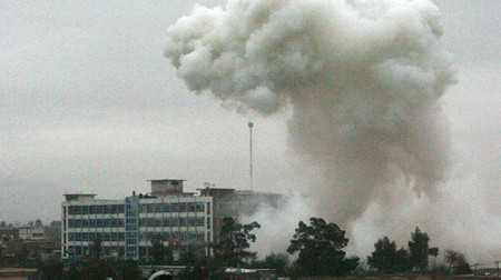 Dust and smoke rise from an explosion in Kandahar as Taliban gunmen and bombers hit a police headquarters